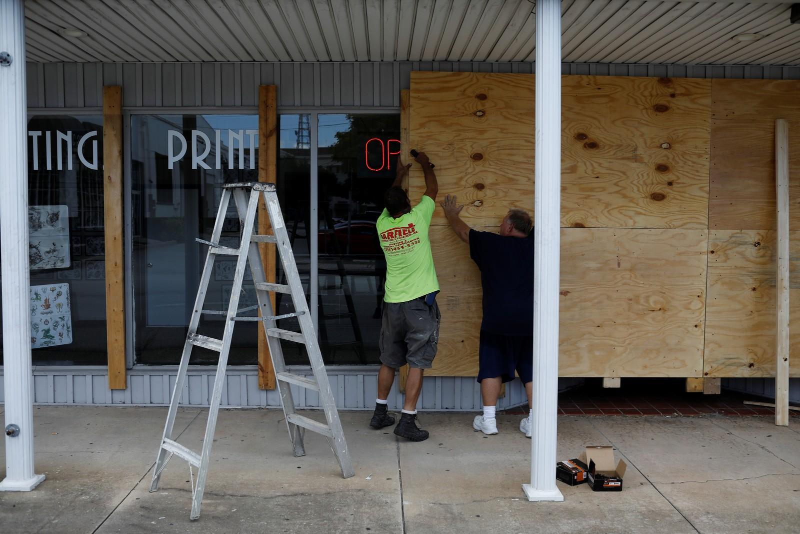Homens colocam painéis em uma loja, na Flórida, após alerta sobre possível chegada do furacão Dorian — Foto: Marco Bello/Reuters