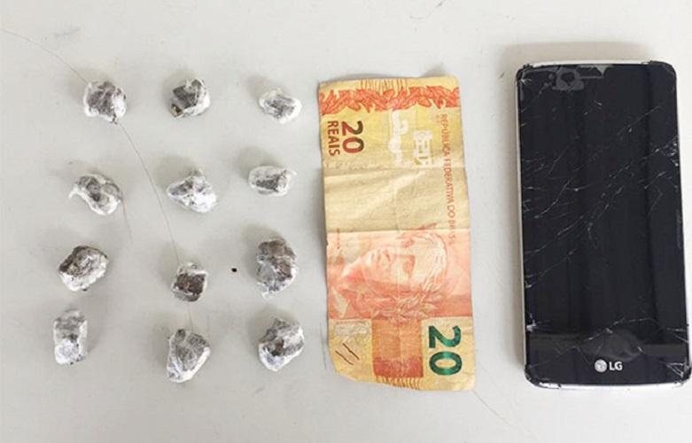 Porção de maconha, dinheiro e aparelho celular foram apreendidos durante a ocorrência — Foto: Cedida/PM
