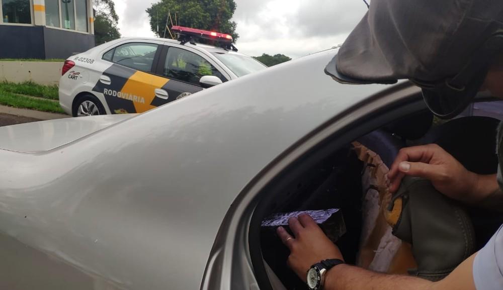 Produtos sem nota fiscal foram encontrados em um fundo falso atrás do banco traseiro do carro — Foto: Polícia Rodoviária/Divulgação