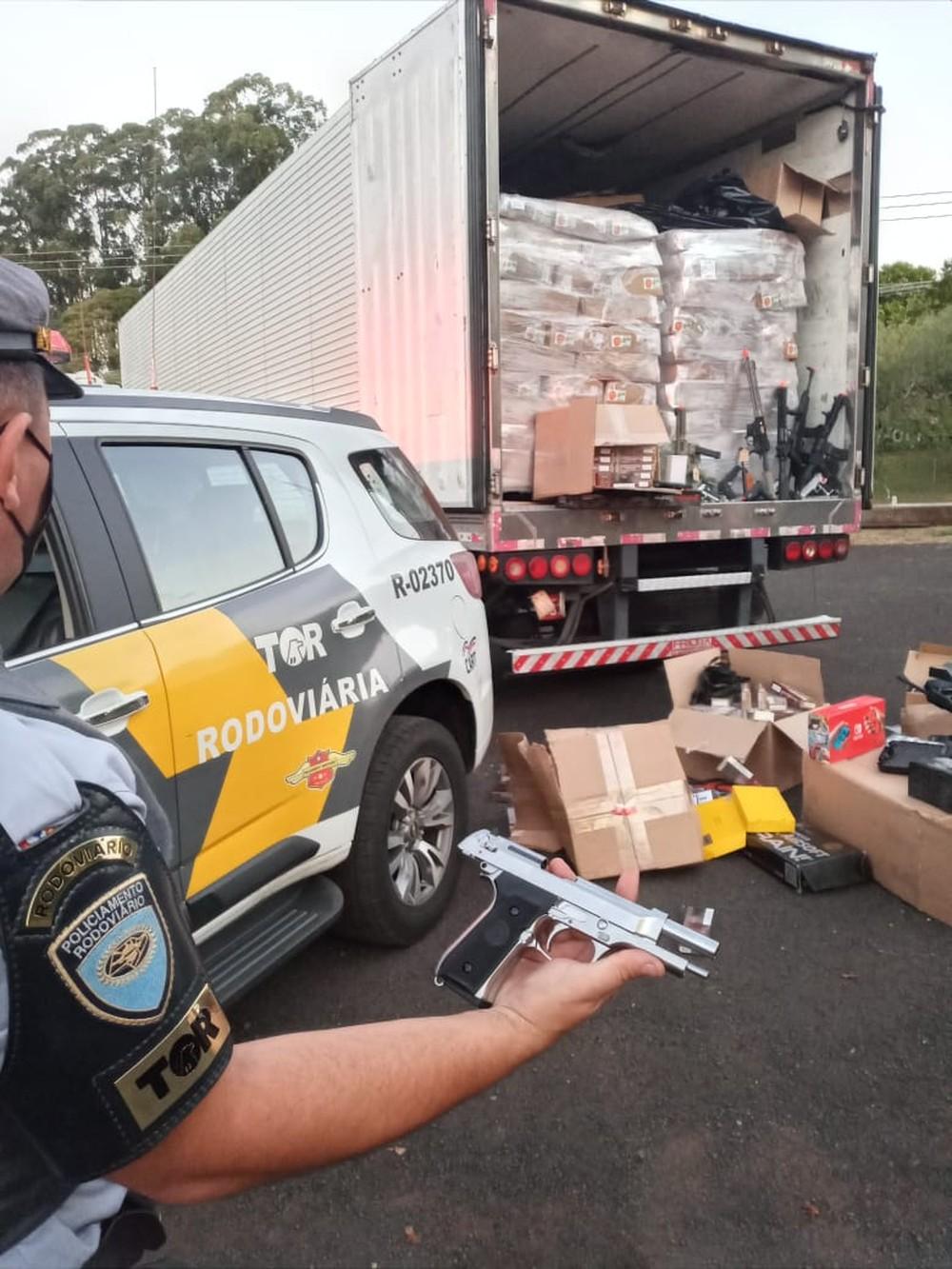 Policial do TOR exibe uma réplica de pistola apreendida; foram apreendidas outras 30 do mesmo tipo — Foto: Polícia Rodoviária/Divulgação